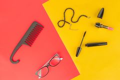 Glasses, cosmetics, jewelry and comb on a yellow and red background. Elegant set of accessory for women. Glasses, cosmetics, jewelry and comb on a yellow and stock images