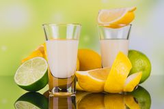 Glasses of cream liqueur with lime and lemon on green background stock photo