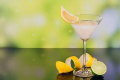 Glasses of cream liqueur with lime and lemon on green background stock images
