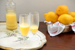 Glasses of crema di limoncello, bottle and lemons. A bottle and two glasses of crema di limoncello on a wooden tray. Some lemons in a wicker basket with a cotton Stock Images