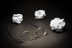 Glasses crumpled paper on black background. Royalty Free Stock Photography