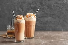 Glasses with delicious caramel frappe. On table Royalty Free Stock Photos