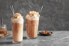 Glasses with delicious caramel frappe. On table Stock Photo
