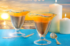 Glasses with dessert and candles at sunset Stock Image