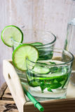 Glasses with detox cucumber water with lime and mint on a wooden tray, pitcher,summer or spring Stock Image