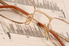Glasses on diagrams Stock Photos