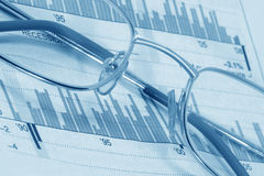 Glasses on diagrams (blue toned). Close up of glasses on diagrams (blue toned Royalty Free Stock Image