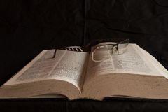 Glasses on dictionary. English dictionary with a pair of glasses resting on it Royalty Free Stock Image