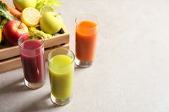 Glasses of different juices and wooden crate with fresh ingredients on table. Space for text stock photo