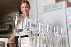 Glasses and dishes from catering. Service with smiling employee Stock Photos