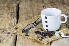 Glasses, earphone,coffee beans and coffee mug on wooden table Stock Photo
