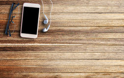 Glasses,earphone and smart phone on brown wooden Stock Photo