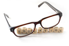 Glasses and education message written in wooden blocks, isolated Stock Photography