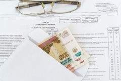 Glasses and an envelope with ruble banknotes  100, 1000, 5000 are on the sheet of accounting of working time. Stock Image