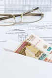Glasses and an envelope with ruble bills lying on the sheet of accounting of working time. Royalty Free Stock Photo