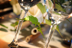 Glasses on event table. A closeup, detailed view of items on a table set for a special event including glass goblets and a leafy centerpiece Royalty Free Stock Image