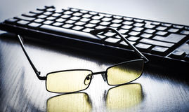 Glasses for eye protection near the keyboard Royalty Free Stock Photography