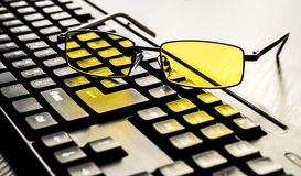 Glasses for eye protection near the keyboard Royalty Free Stock Photos