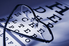Glasses and eye test chart differential focus. Blue tone stock images