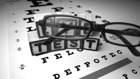 Glasses falling next to blocks spelling out eye test in black and white Stock Photos