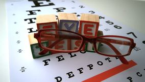 Glasses falling onto eye test with blocks spelling out eye test Royalty Free Stock Image