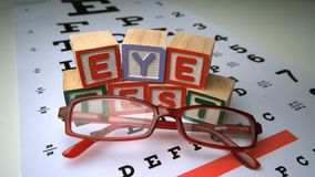Glasses falling onto eye test with wooden blocks spelling out eye test Stock Image