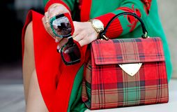 Glasses in female hands. Bag close up. Scottish plaid bag. Stylish modern and feminine image, style. Women`s accessories: watches,