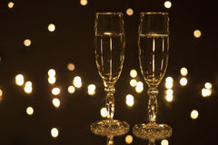 Glasses filled with champagne on a black background in twinkling lights. Two glasses filled with champagne on a black background in the twinkling lights Stock Image