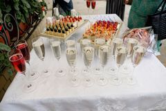Glasses filled with champagne or sparkling wine on a white festive tablecloth background. Festive buffet, corporate event, royalty free stock photography