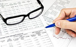 Glasses, financial documents and hand with pencil Royalty Free Stock Photos