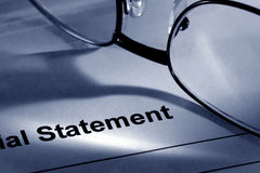 Glasses on Financial Institution Statement Page. Financial institution bank statement with glasses Stock Image