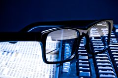 Glasses on financial newspaper Stock Photos
