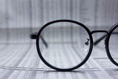 Glasses on financial newspaper under light tint blue Royalty Free Stock Photography