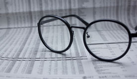 Glasses on financial newspaper under light tint blue Stock Photos