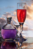 Glasses and flask with sunset background Royalty Free Stock Photo