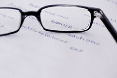 Glasses with focus on bonus. Business words with glasses focusing on bonus Royalty Free Stock Images