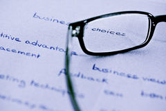 Glasses with focus on business choices. Business words with glasses focusing on business choices, split toned Stock Photos