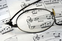 The glasses focus on the music symbols. The glasses focus on the some music symbols royalty free stock photo