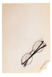 Glasses folded lie on a vintage piece of paper. Glasses folded lie on a vintage piece of paper on a white background Royalty Free Stock Photo