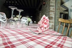 Glasses, fork and knife on red and white checked gingham tablecl Stock Photo