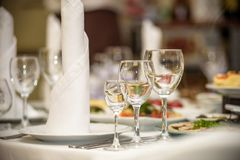 Glasses, forks, knives, napkins and decorative flower on a table served for dinner in cozy restaurant. royalty free stock images