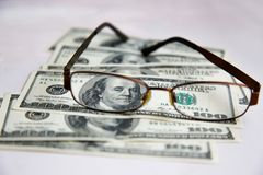 Glasses in a frame lie on dollars spread out on a white table stock photos