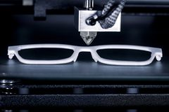 Glasses frame is printed with a 3D printer. Concepts such as cheap eyeglass frames or relief of the health insurance, new production methods of opticians royalty free stock photo