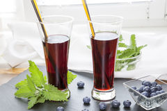 Glasses with fresh Black Currant juice. Bog blueberry and lemon balm Royalty Free Stock Photos
