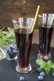Glasses with fresh Black Currant juice. Bog blueberry and lemon balm Stock Image