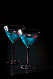 Glasses of fresh blue cocktail with ice on bar table Stock Image