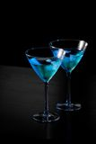 Glasses of fresh blue cocktail with ice on bar table Stock Photography