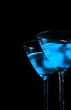 Glasses of fresh blue cocktail with ice on black background royalty free stock photography