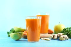 Glasses of fresh carrot juice. On color background Royalty Free Stock Image