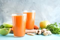 Glasses of fresh carrot juice. On color background Royalty Free Stock Images